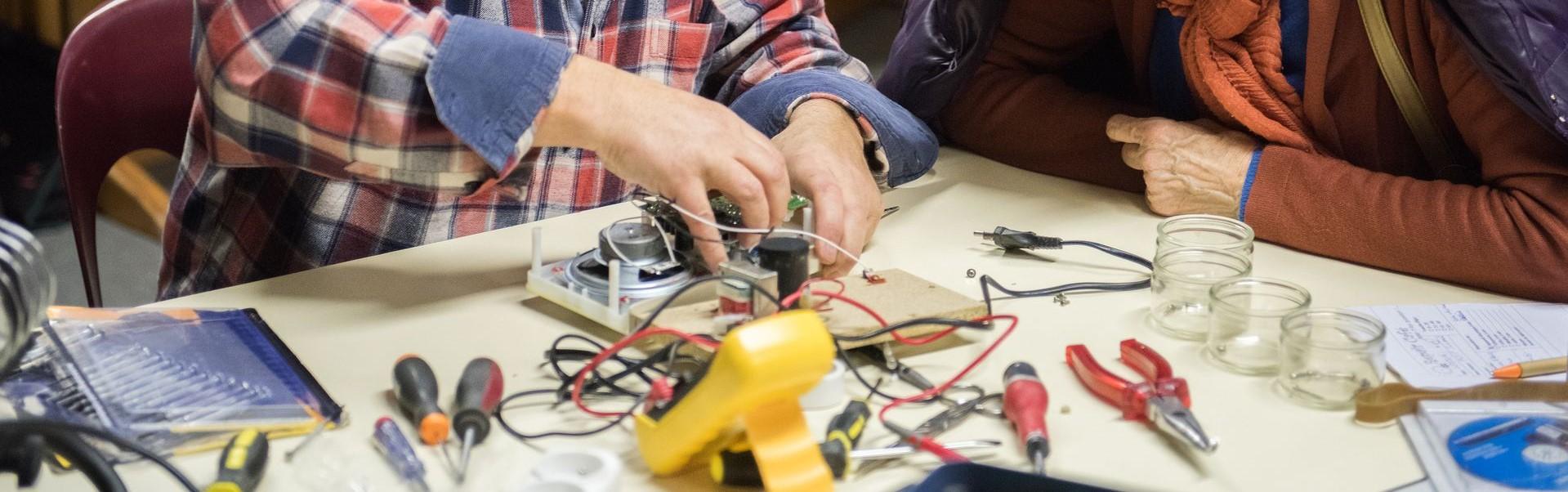 2 mensen werken aan een apparaat dat uit elkaar op tafel ligt